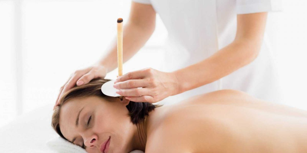 Young woman receiving ear candle treatment from masseur at spa